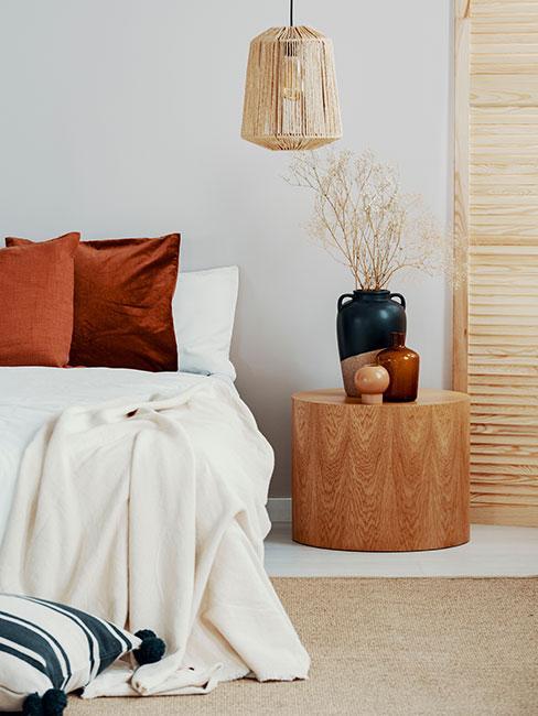 jasna naturalna sypialnia z rattanową lampą i poduszkami w kolorze terakoty