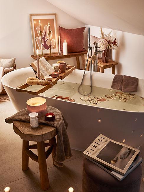 przytulna łazienka z wolnostojącą wanna udekorowaną płatkami róż i dekoracjami w ciepłych kolorach