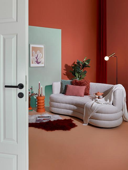 nowoczesny salon z sofą nerką na tle ściany w kolorze terakoty obok dużego fikusa