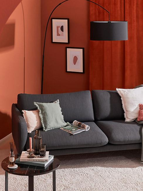 salon z sofą w kolorze grafitowym na tle ściany w kolorze terakoty
