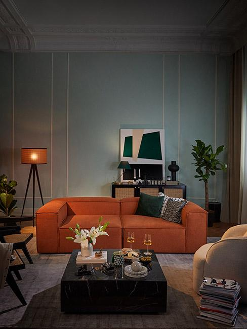 Saon w stylu retro z sofą w kolorze terakoty i ścianą w kolorze błękitu