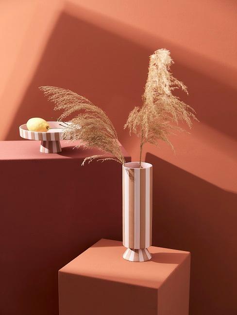 nowoczesne wazony w różowe paski na stolikach w kolorze terakoty