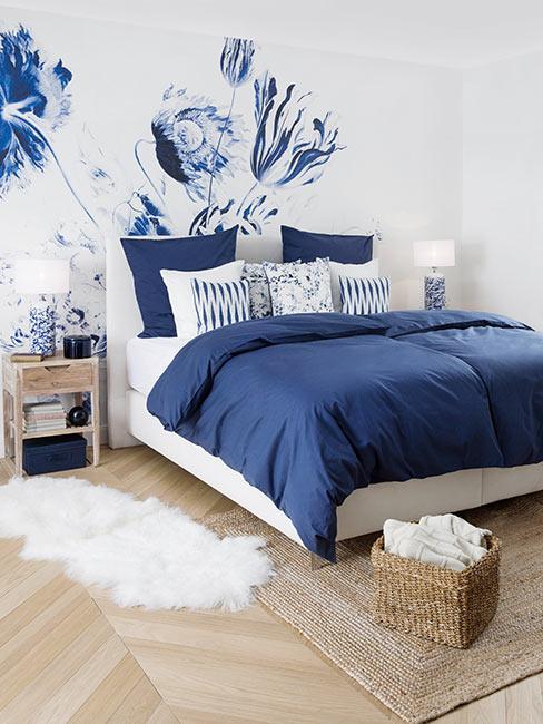 sypialnia w granatowym kolorze, narzuta i poduszki dekoracyjne granatowe, ściana biało-granatowa w delikatne kwiaty