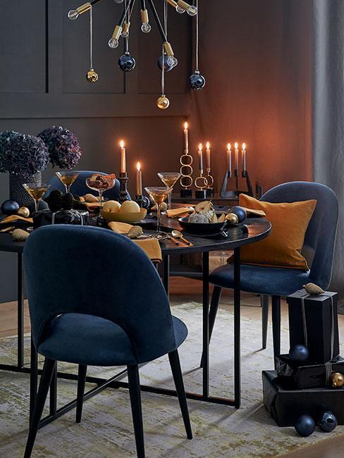 Klimatyczny pokój z zastawionym jedzeniem stołem i zapalonymi świeczkami, granatowe krzesła i jasna podłoga