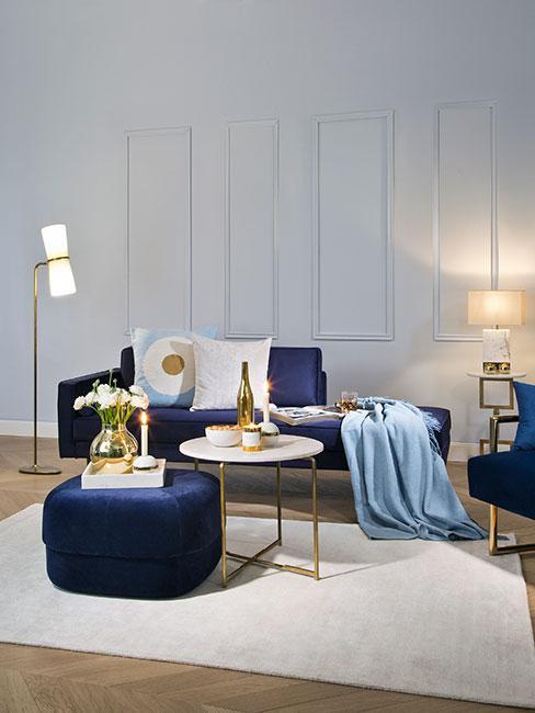 Jasny salon z białą ścianą, drewnianą podłogą i białym dywanem z granatowym akcentem kolorystycznym w postaci sofy oraz pyfa
