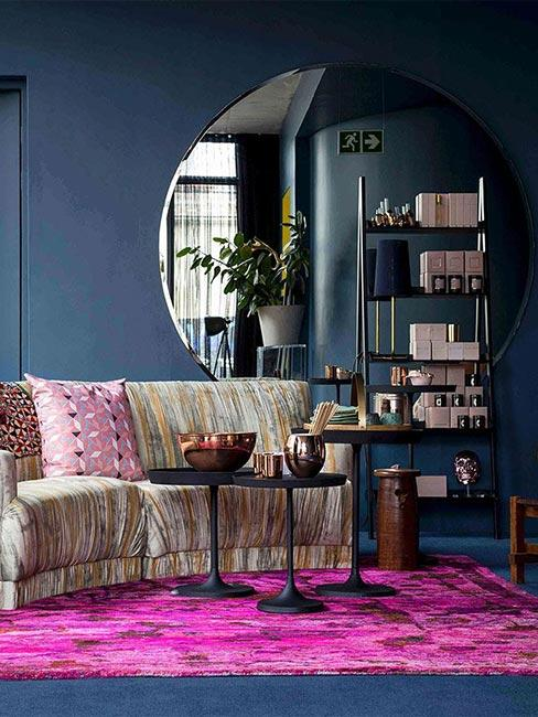 Granatowa ściana zestawiona z intensywnie różowym dywanem i kanapa w jasnym kolorze