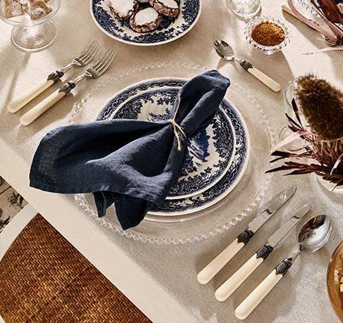 kolor granatowy: zastawa stołowa w kolorze granatowym na stole przykrytym białym obrusem