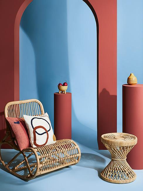 wiklinowy fotel bujany na tle błękitnej ściany z dekoracjami w kolorze terakoty