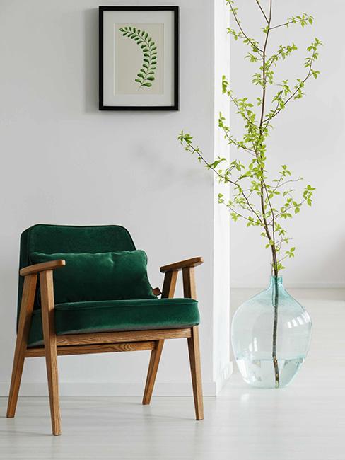 fotel retro z zielonego aksamitu obok wazonu podłogowego z gałązką drzewa