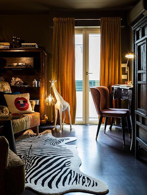 Salon w stylu steampunk, ciemne meble, lampa podłogowa w kształcie małej białej żyrafy trzymającej żarówkę, na podłodze dywan w zebre