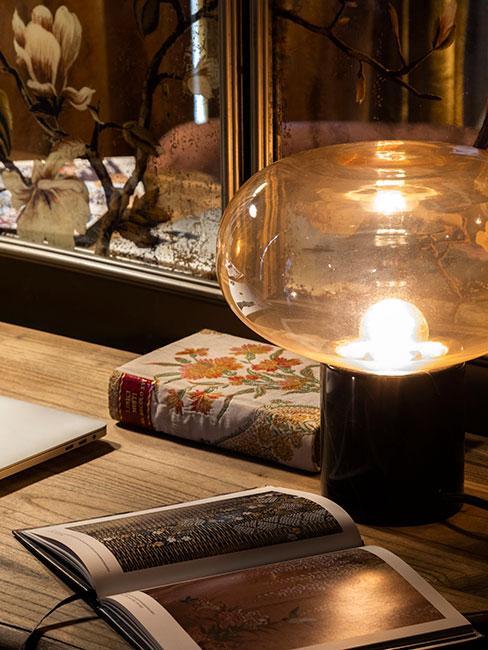 zbliżenie na stolik, na którym leżą albumy i książka w ozdobnej oprawie w kwiaty oraz lampa z czarną podstawą i przeźroczystym kloszem