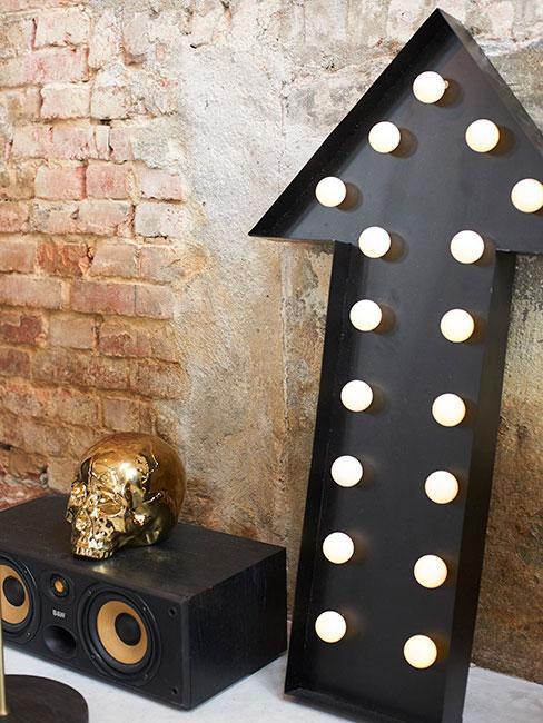 Pomieszczenie w stylu Steampunk, ściana z cegieł, duży czarny znak w kształcie strzałki obok ciemna szafka ze słotą czaszką