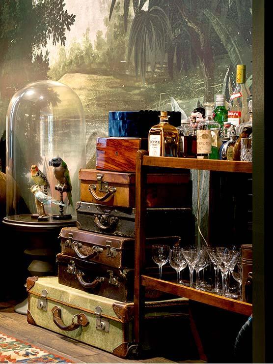 wnętrze w stylu w stylu Steampunk, walizki w starym stylu, oraz półka na alkohole wypełniona alkoholami