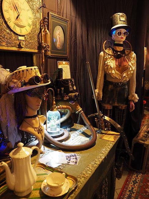Wnętrze w stylu w stylu Steampunk, manekiny w strojach w stylu w stylu Steampunk , ozdobny złoty zegar na ścianie
