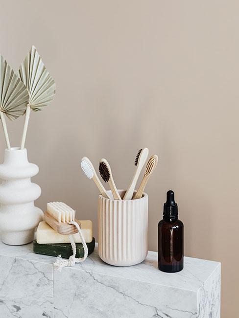 Dodatki łazienkowe na marmurowym blacie na tle ściany w kolorze nude
