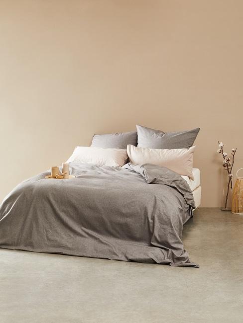 Ściana w kolorze nude z łóżkiem i szarą pościelą