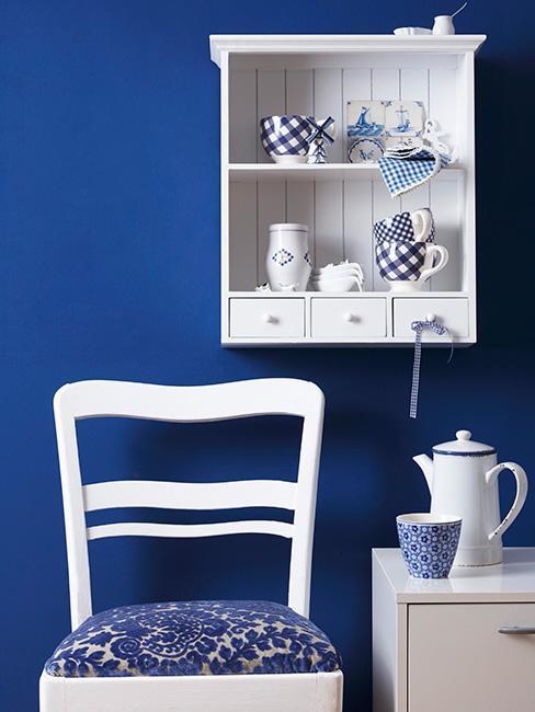 Granatowa ściana w kuchni, na której wisi biała półka z niebieskimi ozdobami, pod spodem białe krzesło i szafka z dzbankiem i filiżanką