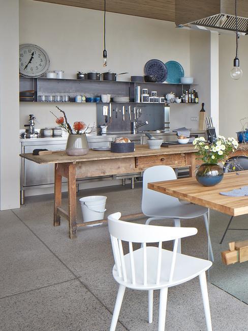 Kuchnia z beżową ścianą, drewnianymi stołami, szafkami w ciemnoszarym kolorze oraz podłogą wyłożoną dużymi szarymi płytkami