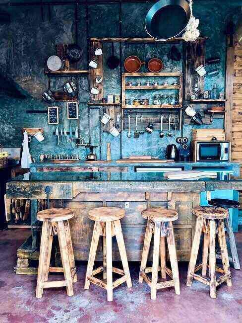 Granatowa kuchnia w stylu vintage, ściana w kolorze niebieskim celowo postarzana, wyspa i stołki barowe drewniane ze śladową ilością farby