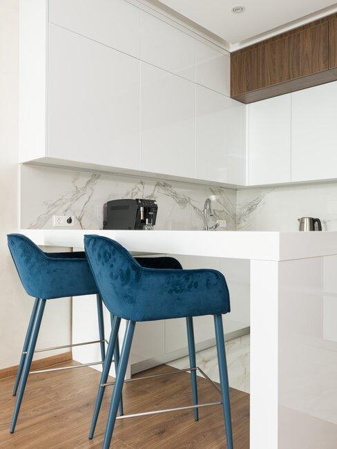 granatowe krzesła w jasnej minimalistycznej kuchni z białymi szafkami i drewnianą podłogą