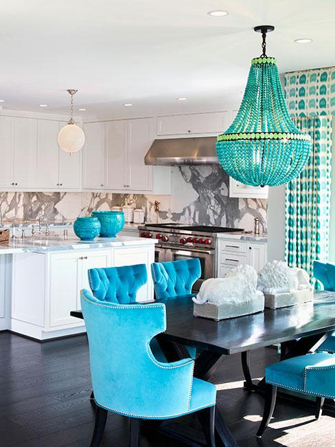 biała kuchnia w stylu retro z niebieskimi akcentami w postaci krzeseł dekoracji i żyrandola