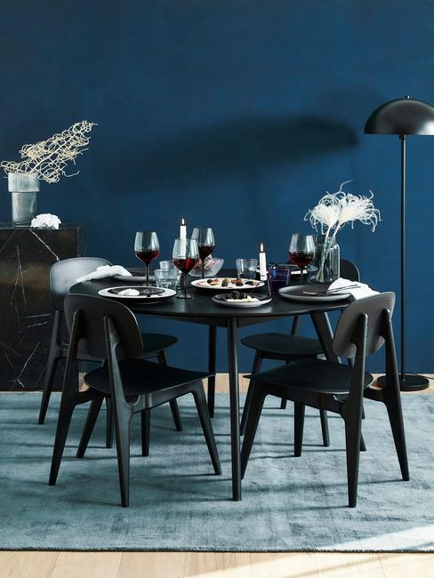 Granatowa kuchnia: ściana w kolorze granatu, stół i krzesła w kolorze ciemnego drewna, jasna podłoga