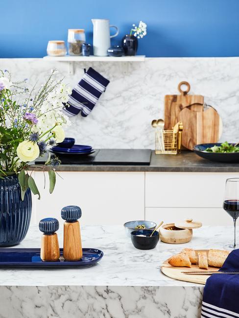 Granatowa kuchnia: dodatki w postaci tacy, rękawicy kuchennej, ściereczki i wazonu w kolorze granatu, na marmurowym blacie w jasnej kuchni