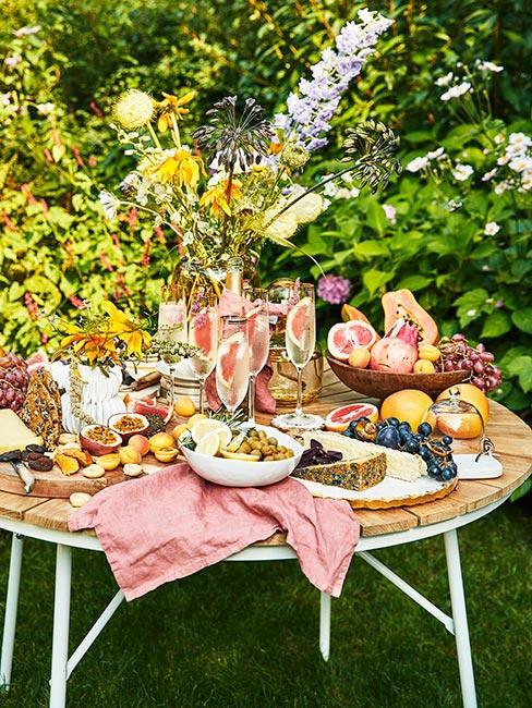 stół w ogrodzie zastawiony świeżymi owocami i koktajlami