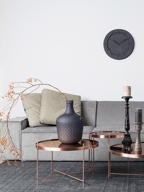 Stoliki kawowe w kolorze miedzi z szarą sofą