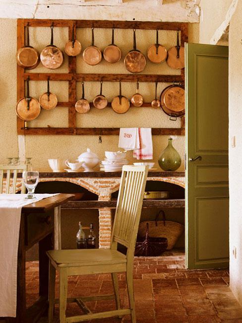 rustykalna kuchnia z miedzianymi garnkami na ścianie i zielonymi meblami