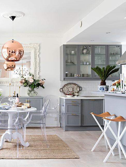 eklektyczna kuchnia z prowansalskimi szarymi szafkami, transparentymi krzesłami i miedzianą lampą