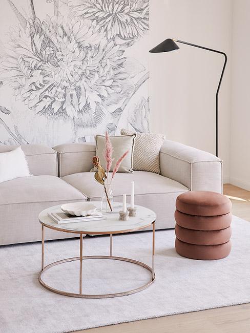salon z beżową sofą modułową na tle jasnoszarej tapety w kwiaty przy miedzianym stoliku kawowym