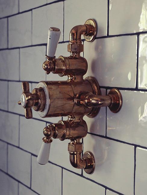 miedziana armatura łazienkowa na ścianie z białymi kafelkami