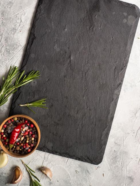 Czarna kamienna deska do krojenia na marmurowym blacie