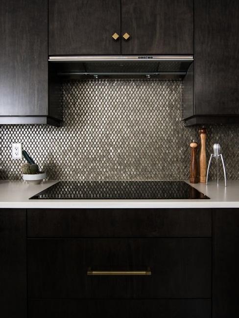 Kuchnia z czarnymi szafkami, jasnym blatem i ciemną mozaiką na ścianie