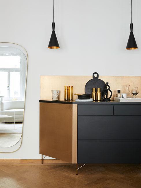 Czarna kuchnia: Kuchnia szafkami z czarnymi frontami i drewnianymi bokami, białą ścianą i dużym lustrem na ścianie
