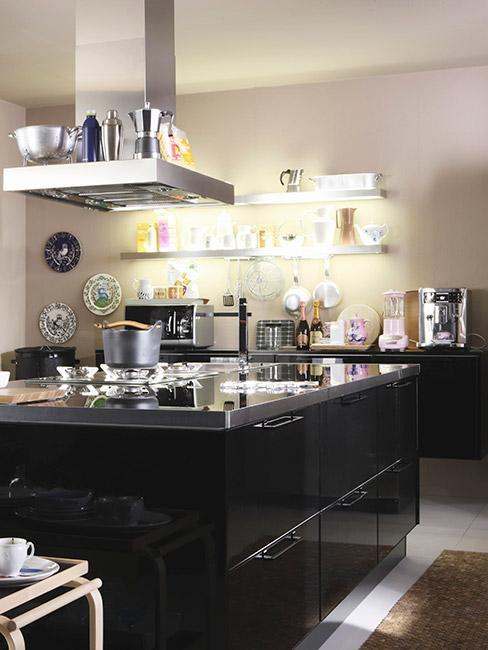 Dobrze oświetlona kuchnia z szafkami i blatami w kolorze czarnym oraz z białymi pólkami na jasnej ścianie