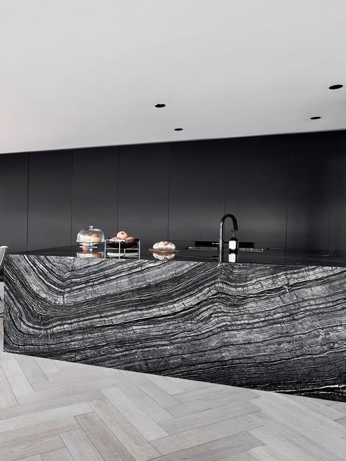 Marmurowe fronty szafek wraz z ciemną ścianą i białym sufitem