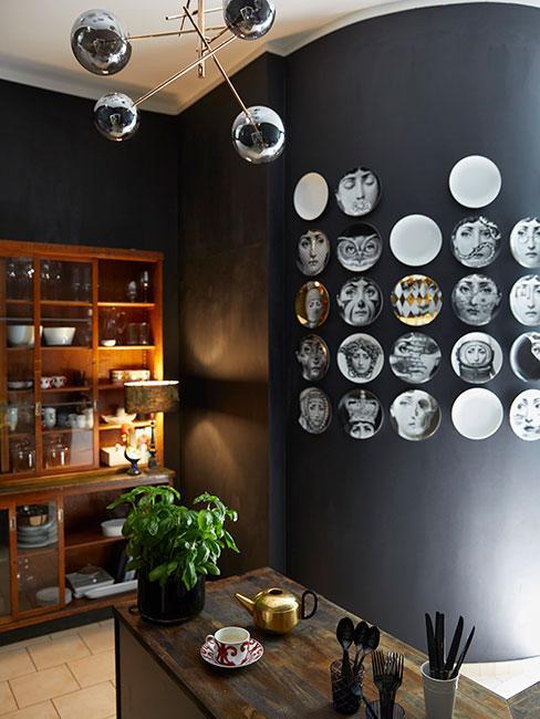 czarna kuchnia z nowoczesną lampą i zdjęciami na czarnej ścianie