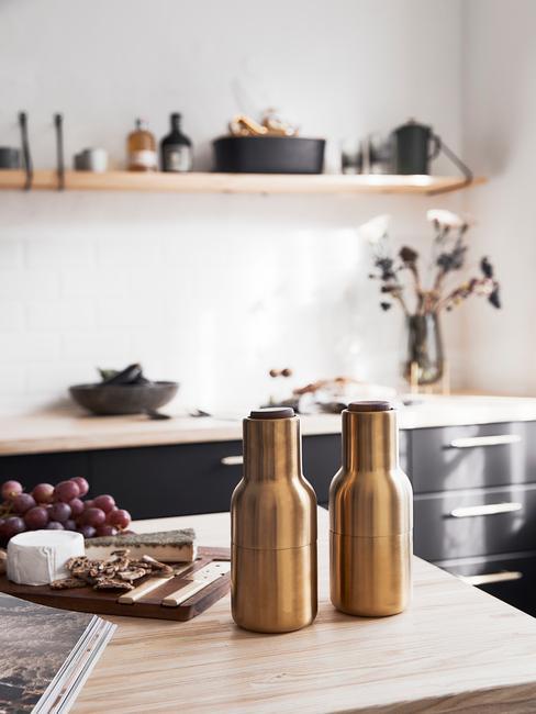 Czarna kuchnia :Złote dodatki w postaci butelek w kuchni czarnej z drewnianymi blatami