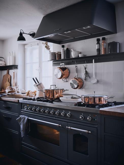 Czarna kuchnia z białymi płytkami naścianie i ciemnymi szafkami wraz ze sprzętem kuchennym