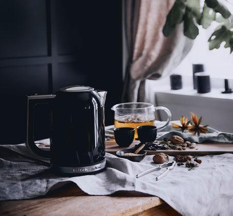 czarna ściana w kuchni ze stołem z drewnianym blatem na którym stoi czarny czajnik