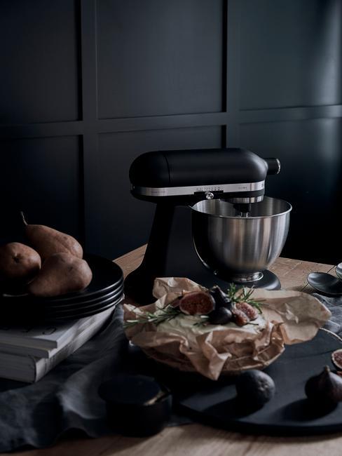 Czarny robot kuchenny na drewnianym stole na tle czarnej ściany