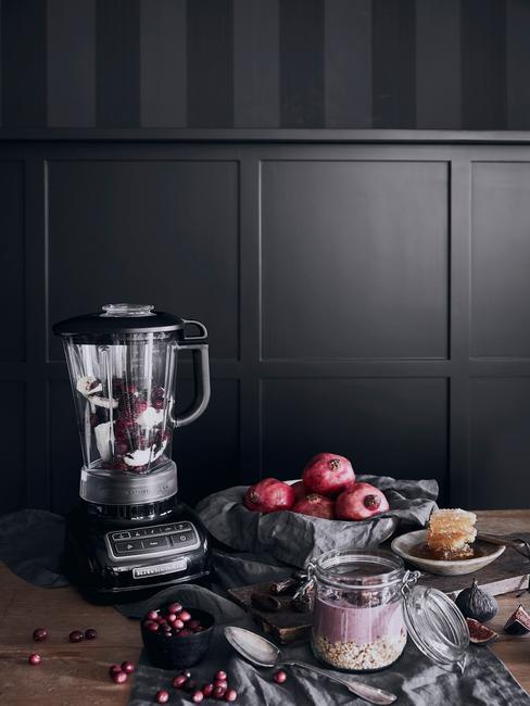 Miksem na drewnianym stole, obok miska z jabłkami na tle czarnej ściany w kuchni