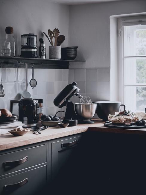 Czarna kuchnia z jasnymi płytkami naścianie, drewnianym blatem i czarnym sprzętem kuchennym