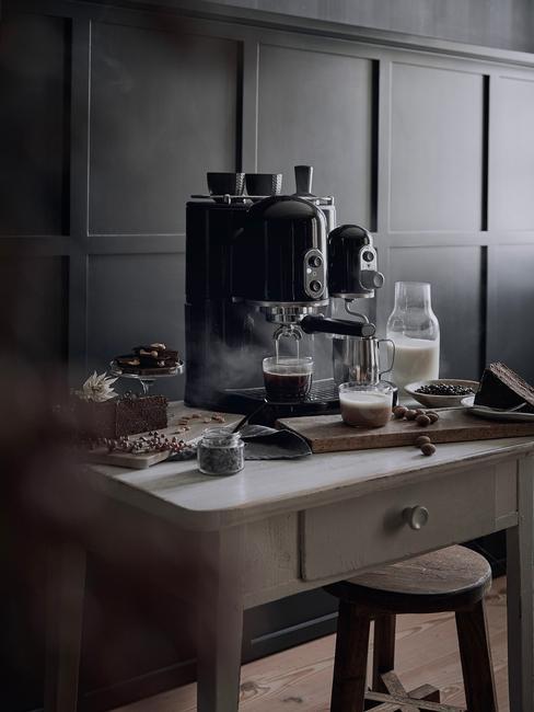 Czarna kuchnia: czarny ekspres do kawy na jasnej konsoli w kuchni na tle czarnej ściany