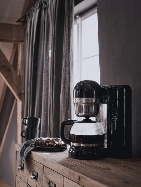 Czarny robot kuchenny w kuchni na drewnianym blacie, w tle ciemne zasłony