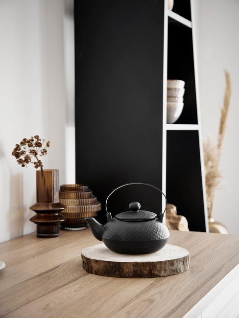 Czarna kuchnia: mały czarny imbryk w japońskim stylu, na drewnianym blacie na tle czarnej szafki w kuchni
