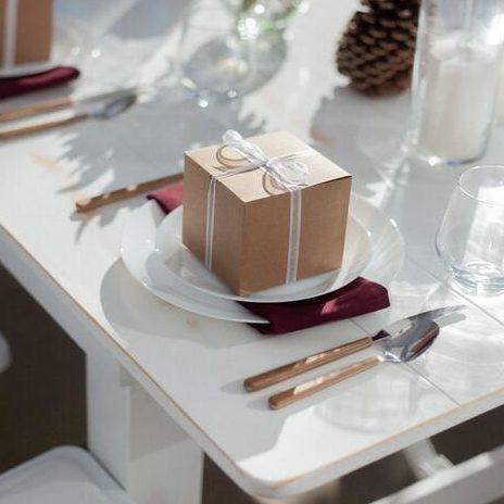 Biała zastawa stołowa na stole, na której położne jest małe małe złote pudełko, które jest prezentem dla gości