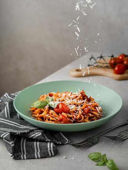 Menu na chrzest: makaron spaghetti w pomidorach, na stole w jasnozielonym talerzu